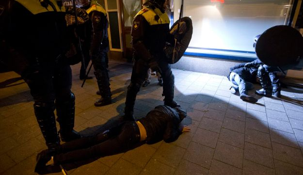 Riot police guard two injured demonstrators after riots broke out near the Turkish consulate in Rotterdam, Netherlands, Sunday, March 12, 2017.