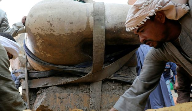 An Egyptian worker prepares the ground before the statue, that might be of revered Pharaoh Ramses II, who ruled Egypt over 3,000 years ago, is raised from the earth, March 13, 2017.
