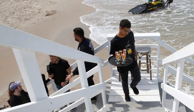 A waiter carries drinks up the stairs of a lifeguard tower renovated into a luxury hotel suite, in Tel Aviv, March 14, 2017.