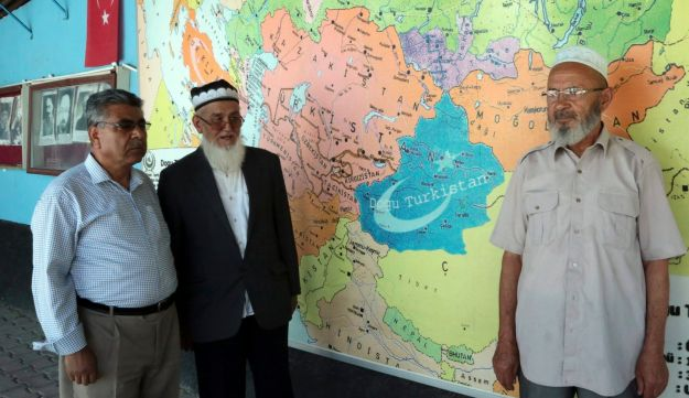 Uighur Muslim men stand in front of map showing the area claimed by Uighur separatists as 'East Turkistan' marked in blue at a resettlement community in Kayseri in central Turkey.
