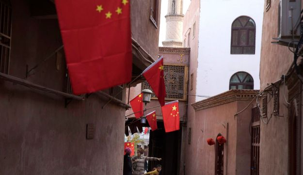 A child reacts to a stranger as adults chat along the corridor of the old city district where Chinese national flags are prominently hung in Kashgar in western China's Xinjiang region.