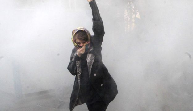 An Iranian woman raises her fist amid the smoke of tear gas at the University of Tehran during ongoing protests. December 30, 2017