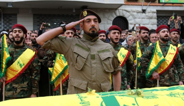 Fighters of the Shiite Hezbollah movement attend the funeral of a comrade who died in combat in Syria during his funeral in the southern Lebanese town of Kfar Hatta on March 18, 2017.