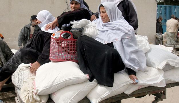Palestinian women sitting on top of sacks of flour on a cart after receiving the monthly food supplies from the UN Relief and Works Agency (UNRWA) in Gaza.