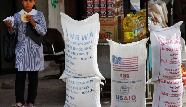 A Palestinian pupil walks past sacks of flour, part of the humanitarian aid provided by UNRWA and USAID, but now offered for sale by a vendor outside a food store in the Shati refugee camp, Gaza City. June 6, 2010