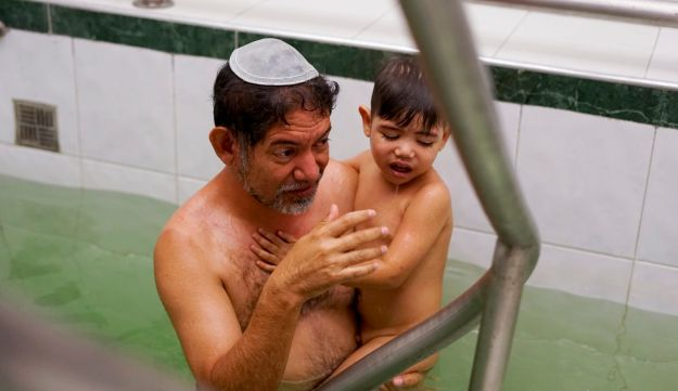 Franklin Perez dips his son in a ritual bath to mark their conversion to Judaism in Bogota, Colombia, March 19, 2017.