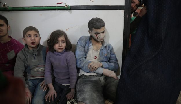 Syrian children wait to receive treatment at a makeshift clinic following reported air strikes by government forces in the rebel-held town of Douma, on the eastern outskirts of Damascus, on April 4, 2017.