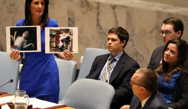 U.S. envoy to the UN Nikki Haley holds photographs of victims during a UN Security Council meeting on Syria, April 5, 2017.