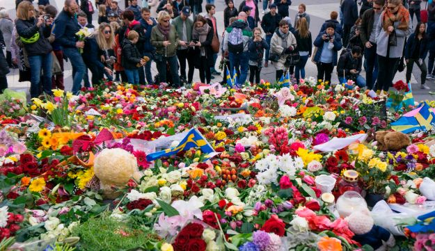 People gather on April 9, 2017 at a makeshift memorial near the point where a truck drove into a department store in Stockholm, Sweden.