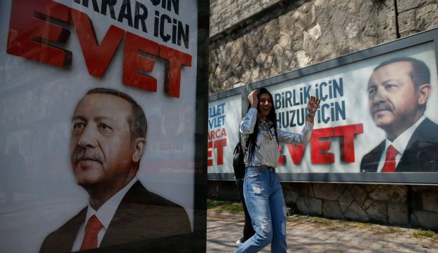 "A Turk walking past ""Yes"" billboards with images of Turkey's president, Recep Tayyip Erdogan, in Istanbul, Friday, April 14, 2017."