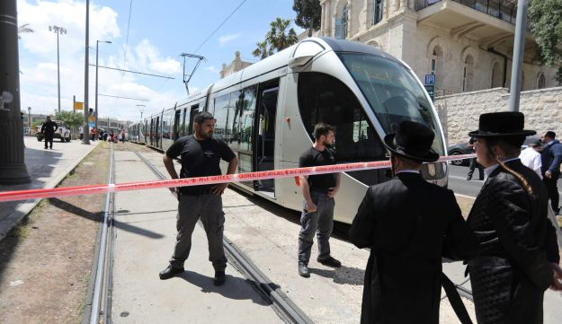 Israeli policemen block a road where the light train passes following a stabbing attack just outside Jerusalem's Old City, according to Israeli police April 14, 2017.
