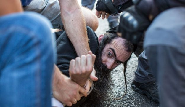 Yishai Schlissel is apprehended by police moments after stabbing several people at the Jerusalem Gay Pride parade, July 30, 2015.