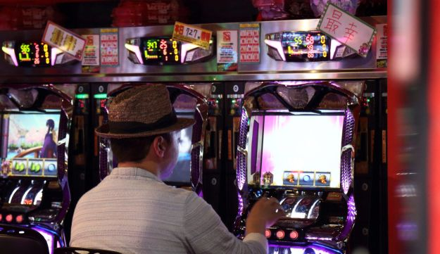 A customer playing a slot machine in a pachinko parlor in Tokyo, Japan.