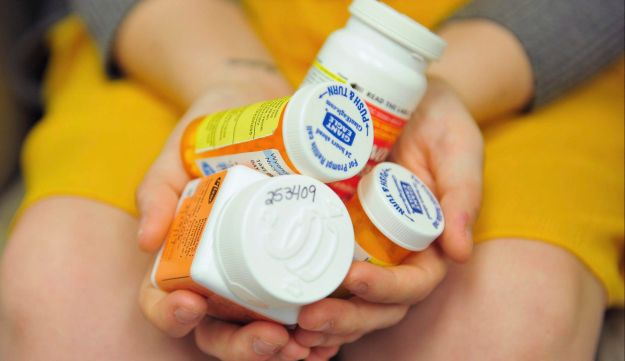 An American woman who became addicted to opioid painkillers holding a handful of her medication bottles.