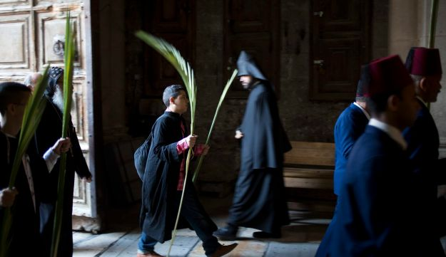 Christians hold palm fonds during the Palm Sunday mass inside the Church of the Holy Sepulchre, April 9, 2017.
