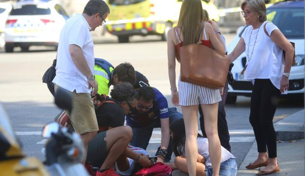 An injured person is treated in Barcelona after a van plowed into pedestrians in the city center, August 17, 2017.