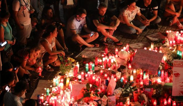 People gather around an impromptu memorial a day after a van crashed into pedestrians at Las Ramblas in Barcelona, Spain August 18, 2017.