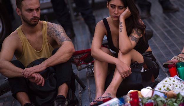 People sit next to candles and flowers placed on the ground after a terror attack that killed 14 people and wounded over 120 in Barcelona, Spain, Sunday, Aug. 20, 2017