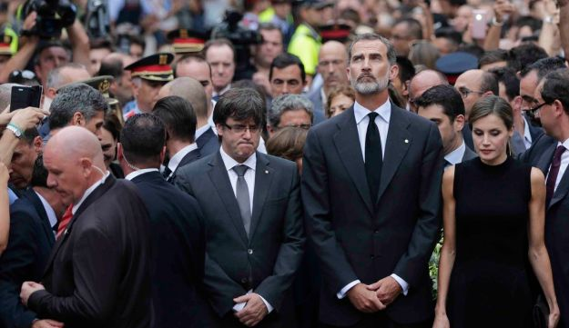 Spain's King Felipe stands with Queen Letizia and Catalonia regional President Carles Puigdemont at a memorial  to the van attack victims in Las Ramblas promenade, Barcelona, Spain, Aug. 19, 2017.