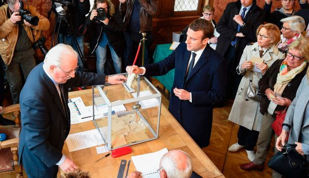 French presidential election candidate movement Emmanuel Macron casts his ballot at a polling station in Le Touquet, northern France, on April 23, 2017.