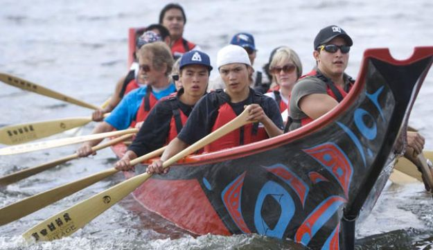 Traditional Tlingit canoe,brightly colored and decorated, bearing what seems to be nine people
