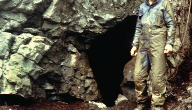 Timothy H. Heaton at the entrance of the On Your Knees Cave. The archaeologist is wearing a yellow hard hat.