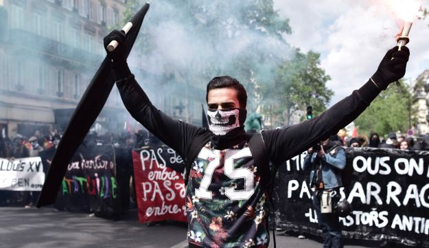 A man holds a flags and smoke flare as he leads a march during the protest for the annual May Day workers' rally in Paris on May 1, 2017.