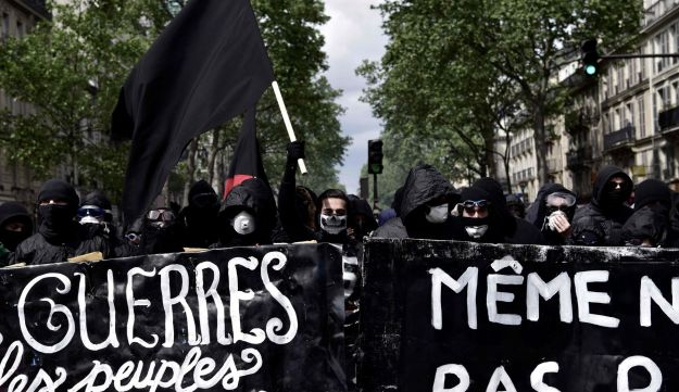 Demonstrators hold banners during a protest march for the annual May Day workers' rally in Paris on May 1, 2017.