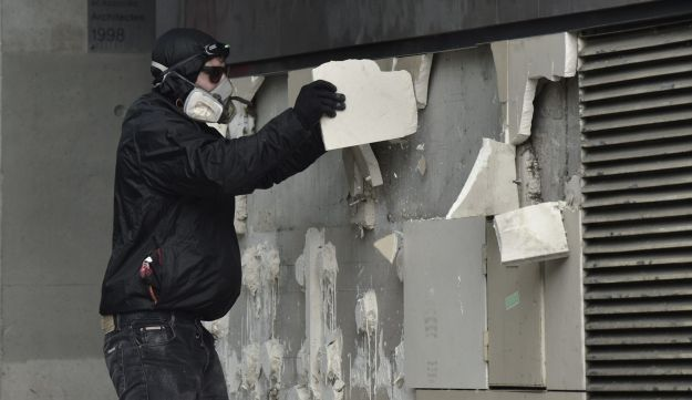 A protester remove stones from the facade of a building during a march for the annual May Day workers' rally in Paris on May 1, 2017.