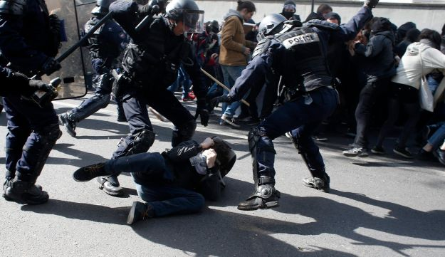 Riot police officers arrest a demonstrator as part of the May Day march, Monday May 1, 2017, in Paris.