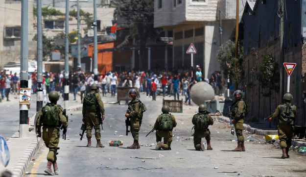 Palestinians throw stones towards Israeli troops during clashes after a protest in support of Palestinian prisoners on hunger strike in Israeli jails, in the West Bank village of Beita, southeast of Nablus city, Friday, May 12, 2017. (AP Photo/Majdi Mohammed)