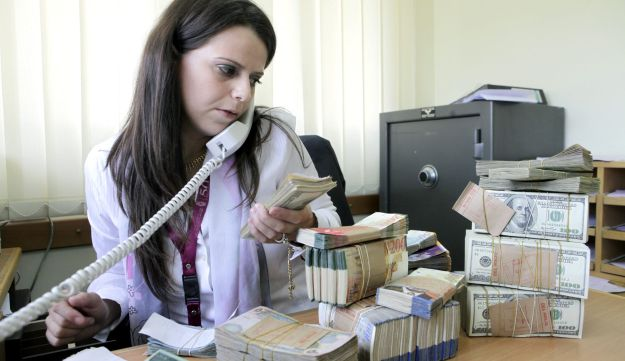 FILE PHOTO: A teller at the Bank of Palestine Plc counts U.S. dollar notes at her desk in a branch of the bank in Bethlehem, West Bank, on Monday, Aug. 1, 2011.