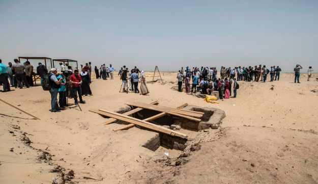Journalists gather on May 13, 2017, outside catacombs in the Touna el-Gabal district of the Minya province, in central Egypt, where Egyptian archaeologists discovered non-royal mummies