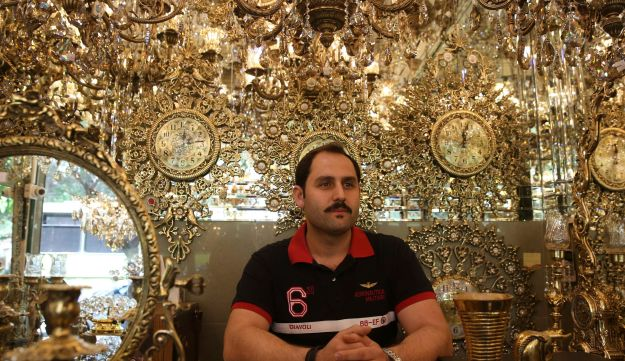 In this Saturday, May 6, 2017 photo, Hamidreza Ghorbanpour, 31, a chandelier trader is interviewed by The Associated Press about Iran's upcoming presidential election at his store, in Tehran, Iran.