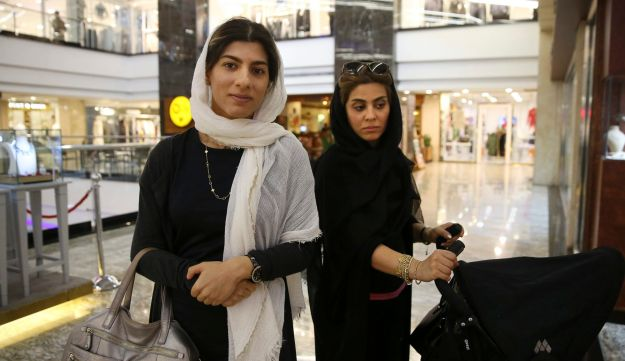 In this Sunday, May 7, 2017 photo, Maryam Amir Moezi, 26, left, a dentist is interviewed by The Associated Press about Iran's presidential election, in the Palladium shopping center, in Tehran, Iran.