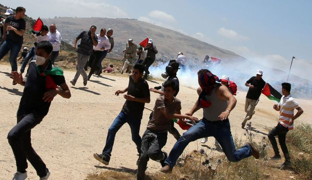 Palestinian demonstrators run for cover during clashes with Israeli forces following a protest in support of Palestinian prisoners on hunger strike in Israeli jails, in the West Bank village of Bait Djan, near the city of Nablus, on May 19, 2017