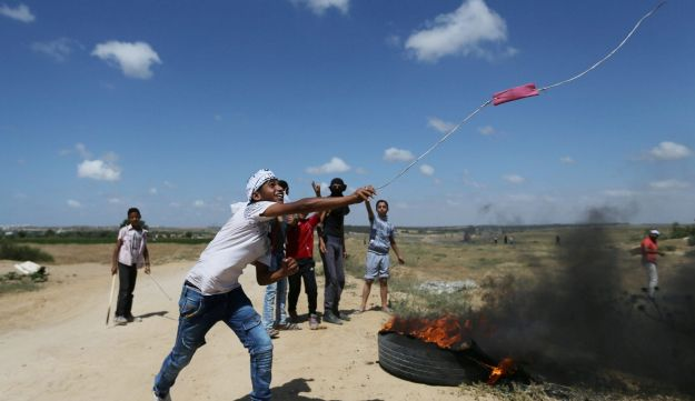 A Palestinian protester uses a sling to hurl stones at Israeli troops during clashes following a protest against the blockade on Gaza, near the border between Israel and Central Gaza Strip May 19, 2017.