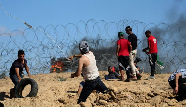 Palestinian protesters hurl stones at Israeli troops following a protest against the blockade on Gaza, near the border between Israel and Central Gaza Strip May 19, 2017.