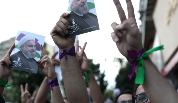 Supporters of newly re-elected Iranian President Hassan Rouhani hold placards bearing a portrait of him as they take to the streets to celebrate his victory in downtown Tehran on May 20, 2017.