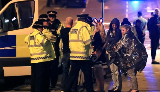 Emergency services personnel speak to people outside Manchester Arena after an explosion at the venue, May 22, 2017.