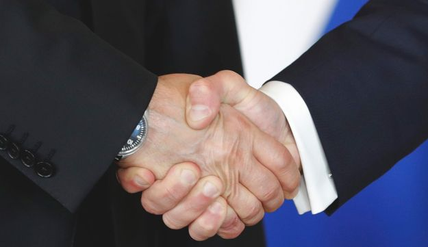 French President Emmanuel Macron, right, shakes hands with his Russian counterpart Vladimir Putin.