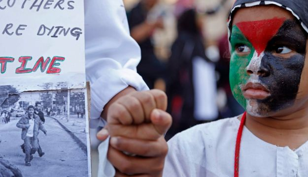 A child with a Palestinian flag painted on its face along with Palestinian supporters takies part in a rally against the Israeli occupation of the Palestinian territories in Cape Town, South Africa, Saturday, Aug. 9, 2014. Thousands of anti-Israel protestors took to the streets marching on the South African parliament building to protest against Israeli occupation and strikes on Gaza, in recent time.