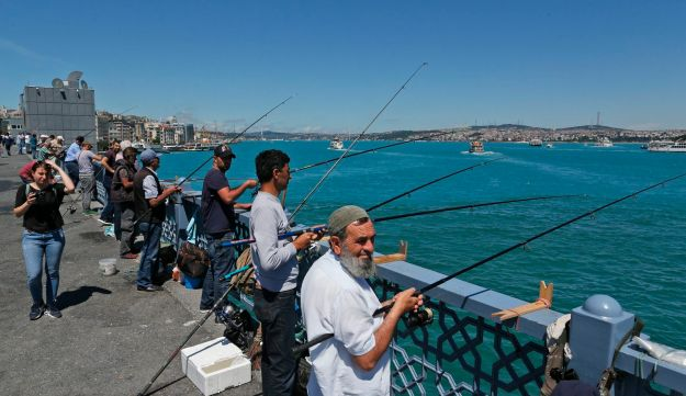 People trying to catch fish on a bridge over Istanbul's Golden Horn that leads to the Bosporus, June 13, 2017.
