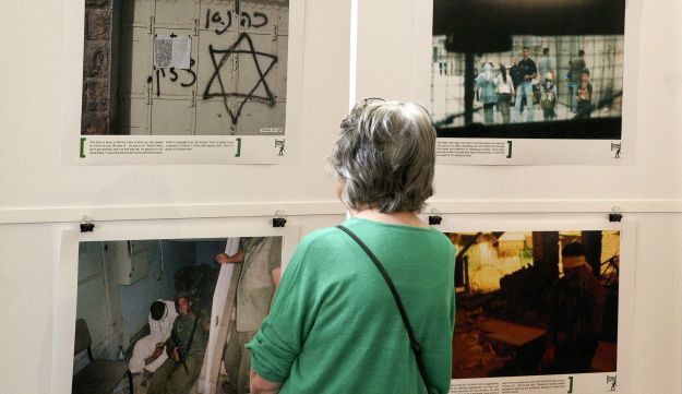 A visitor looks at the 'Breaking the Silence' exhibition at the Kulturhaus Helferei, Zurich. June 8, 2015