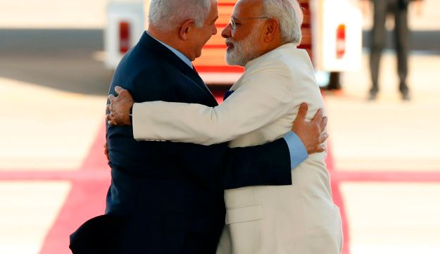 Israeli Prime Minister Benjamin Netanyahu (L) greets his Indian counterpart Narendra Modi (R) during an official ceremoney at Ben-Gurion International airport near Tel Aviv on July 4, 2017.  Modi is the first Indian prime minister to visit Israel, the result of growing ties that have led to billions of dollars in defence deals. / AFP PHOTO / Jack GUEZ