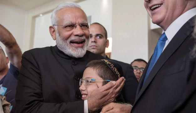Indian Prime Minister Narendra Modi (L) stands next to Israeli Prime Minister Benjamin Netanyahu, as he hugs Moshe Holtzberg, whose parents were killed during the November 2008 attacks in Mumbai at Nariman House, home to the Mumbai chapter of the Chabad-Lubavitch Jewish movement, in Jerusalem July 5, 2017. REUTERS/Atef Safadi/Pool