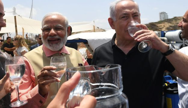 Indian Prime Minister Narendra Modi and Prime Minister Benjamin Netanyahu enjoy a glass of water during their visit to a mobile desalination unit on July 6, 2017.