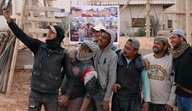 """Members of """"You Destroy and We Rebuild Brigade"""" take a selfie at a construction site, in the rebel-held town of Saida, in Deraa province, Syria May 24, 2017. Picture taken May 24, 2017. REUTERS/Alaa Al-Faqir"""