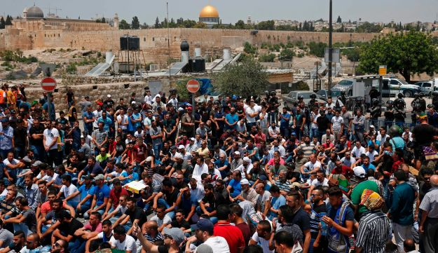 Palestinian worshippers sit outside Jerusalem's Old City after Israeli police barred men under 50 from entering the Old City for Friday Muslim prayers. July 21, 2017.