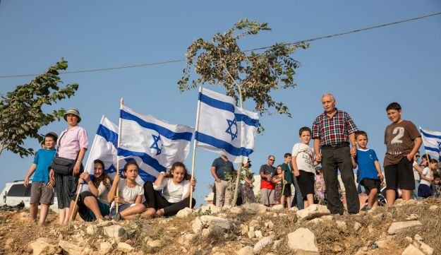 Elazar, by Netiv Ha'avot: Picture shows a bunch of people, some of clearly minors, standing and sitting on rather rocky ground. We also see three Israeli flags and two possibly rather newly planted trees.